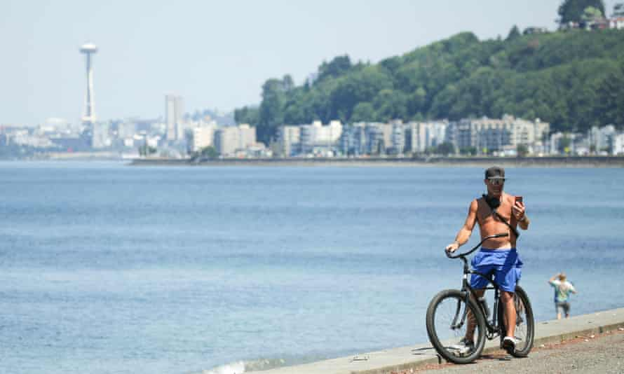 A cyclist rides along the seashore during record-breaking temperatures in Seattle, Washington.