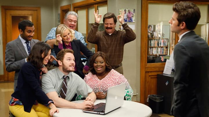 The cast of Parks and Recreation laughing at a computer.