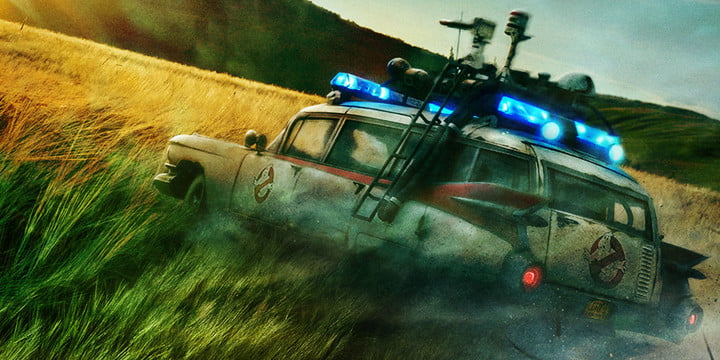 The famous Ecto-1 Ghostbusters car driving through a field.