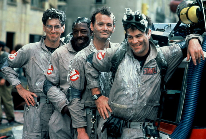 All four original Ghostbusters stand in a line covered in slime.