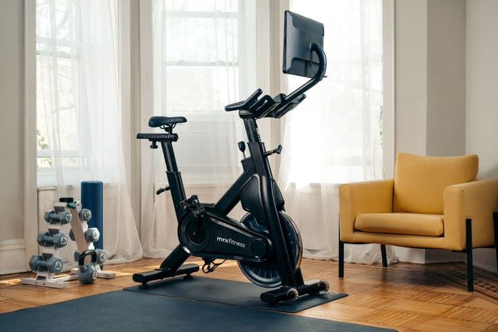 MYX II bike indoors with exercise mat and dumbbells.