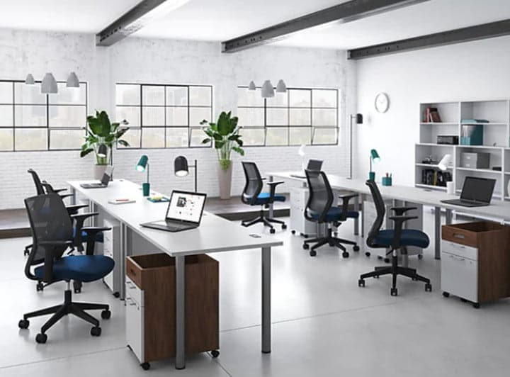 A bright office with multiple chairs at long desks.