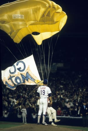 Actor Mike Sergio parachutes onto the field in the first round of Game 1 of the 1986 World Series.