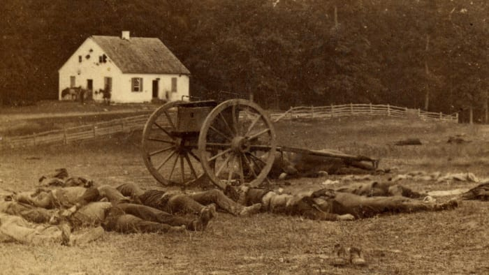 Several dead Confederate gunners lie outside Dunker Church after the Battle of Antietam. The church was the site of some of the bloodiest fighting in the battle. September 19, 1862.