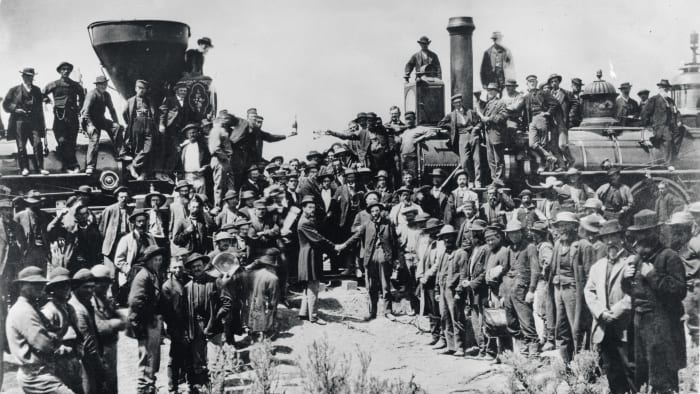 Railroad workers celebrate and pose for a photo at the Golden Spike Ceremony in Utah on May 10, 1869, signifying the completion of the first transcontinental rail route created by joining the Central Pacific and Union Pacific Railways.