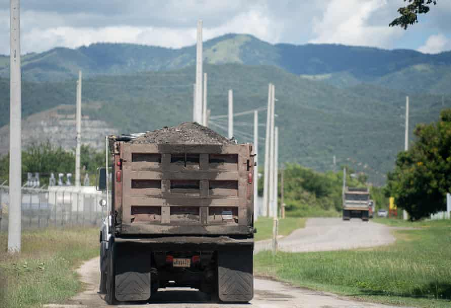 Dump trucks leave the AES coal-burning power plant, known as La Carbonera by locals, in Guayama.