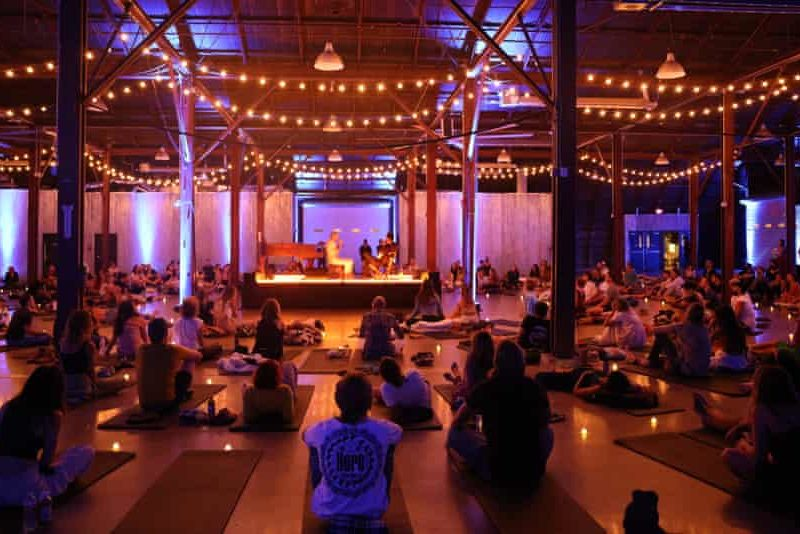 East Forest and Jon Hopkins on stage in Austin, surrounded by people on yoga mats