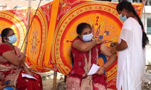 A health worker inoculates a woman with a dose of coronavirus vaccine at a temporary vaccination camp set up in Chennai.