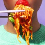 Chopsticks are lifting noodles that are being eating by red lips