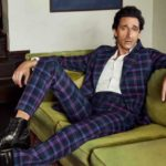 Check mate: Adrien wears suit by Vivienne Westwood, shirt by Thom Browne, boots by Carvil, bracelet by Atelium and ring by Bulgari