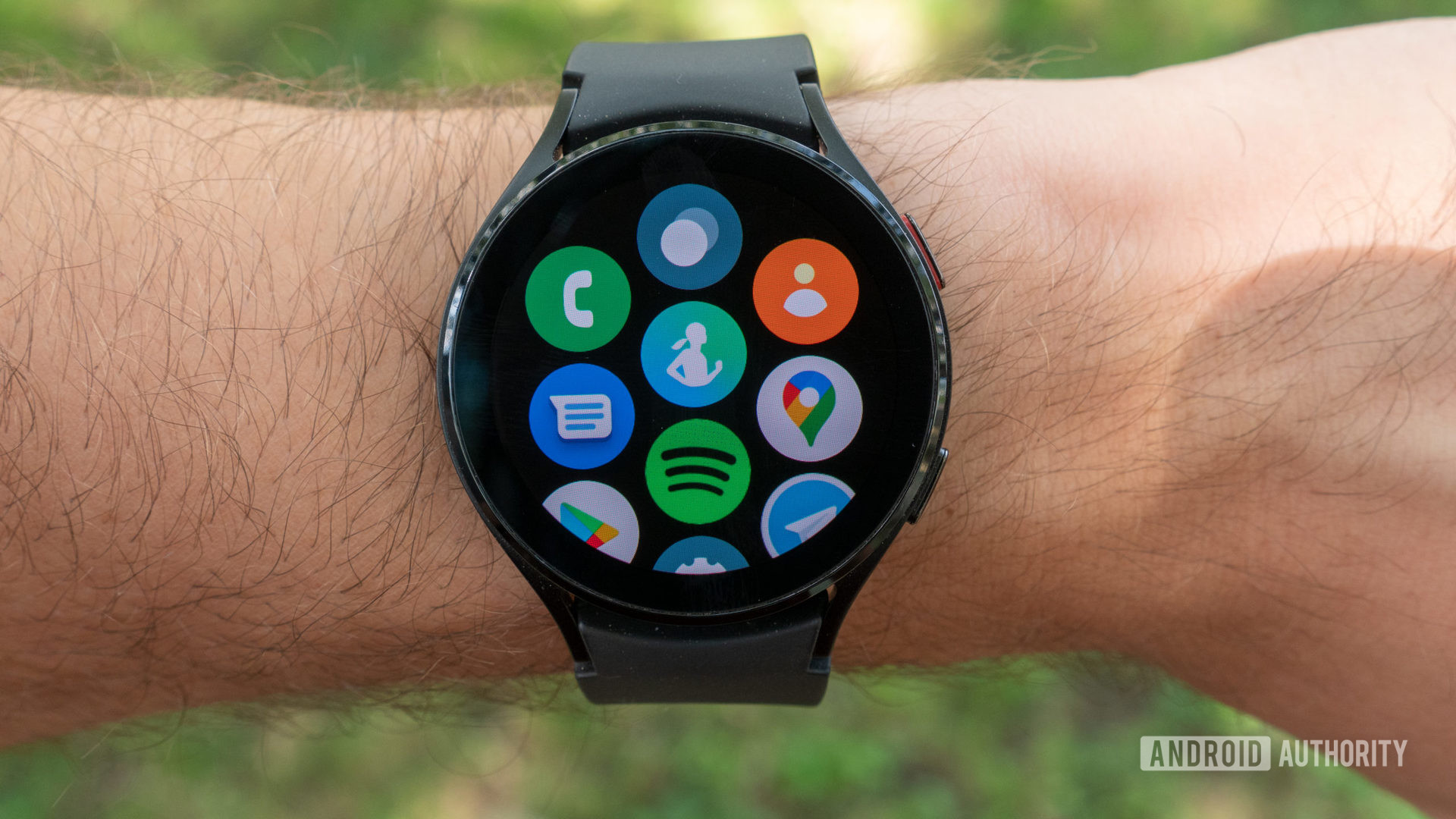 The Samsung Galaxy Watch 4 on a man's wrist showing the all-apps page.